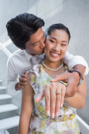 Couple showing engagement ring on womans finger on the stairs photo
