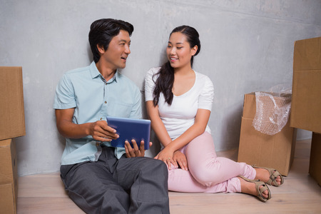 Happy couple sitting on floor using tablet surrounded by boxes in their new home photo