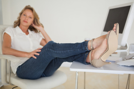 Casual businesswoman sitting at her desk with feet up in her office