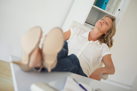 Casual businesswoman sitting at her desk with feet up in her office photo