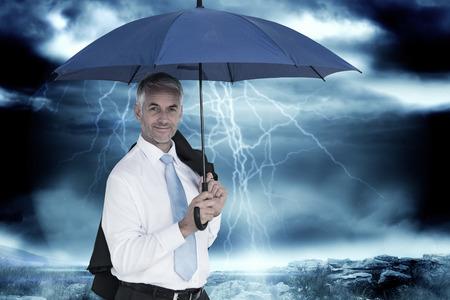 Businessman holding blue umbrella against stormy dark sky with lightning bolts photo