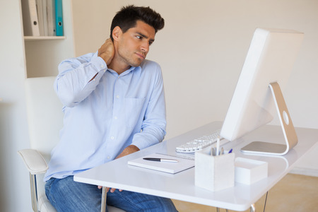 Casual businessman touching his sore neck in his office Stock Photo