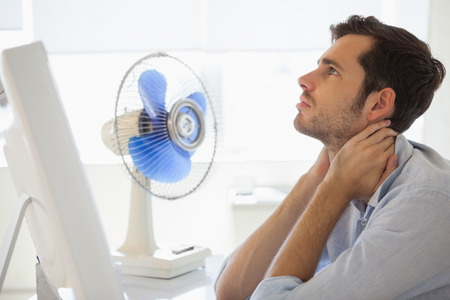 Casual businessman sitting at desk with electric fan in his office photo