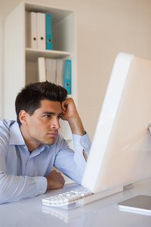 slumped: Casual businessman slumped at his desk in his office