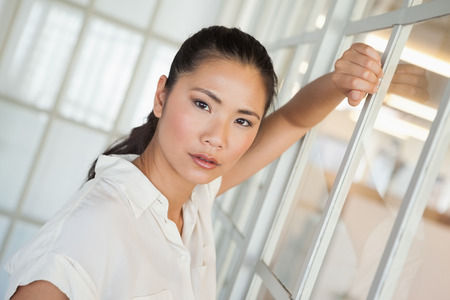 unsmiling: Casual frowning businesswoman leaning on window in the office