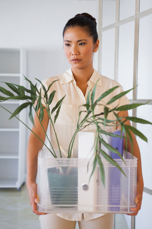 well laid: Fired businesswoman holding box of her things in the office Stock Photo