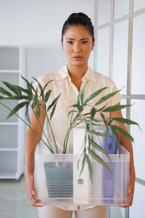 Fired businesswoman holding box of her things in the office photo