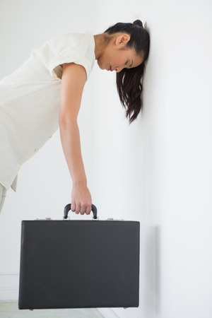 bowed head: Casual businesswoman leaning against wall with briefcase in the office Stock Photo