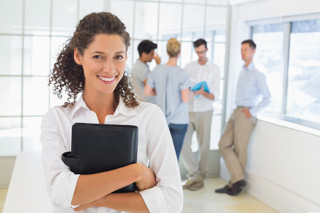 Casual businesswoman smiling at camera holding diary in the office photo