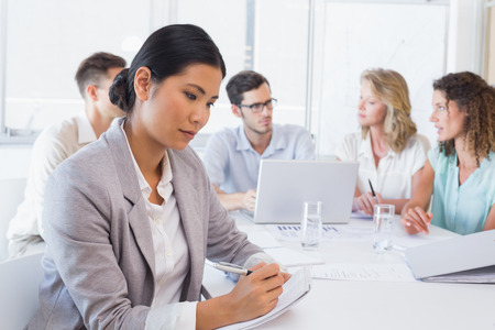Casual businesswoman taking notes during meeting in the office photo