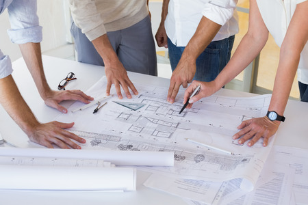 female architect: Casual architecture team working together at desk in the office