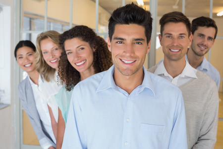 business casual: Casual business team smiling at camera together in the office Stock Photo