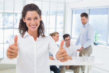 Casual happy businesswoman showing thumbs up to camera in the office photo