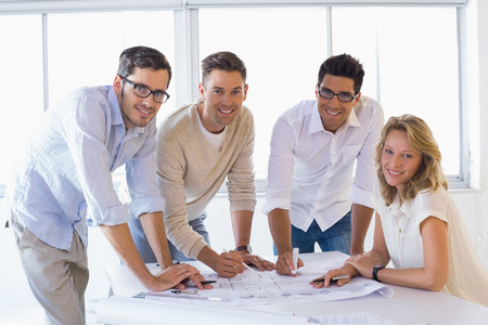 Casual architecture team working together smiling at camera in the office photo