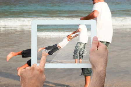 Hand holding tablet pc showing father and son having fun at the beach photo