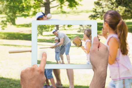 Hand holding tablet pc showing father playing baseball with his children photo