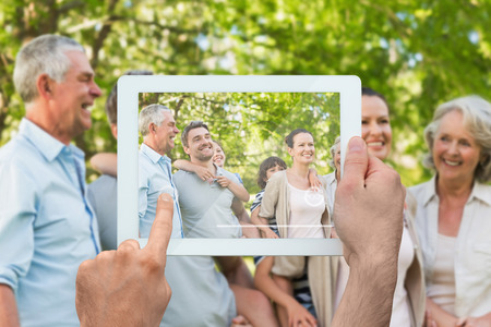 Hand holding tablet pc showing extended family spending time in the park photo