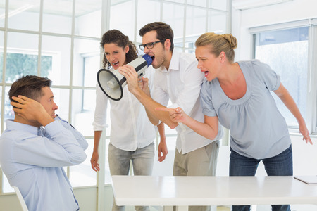 businessman using a megaphone: Casual business team shouting at a colleague in the office