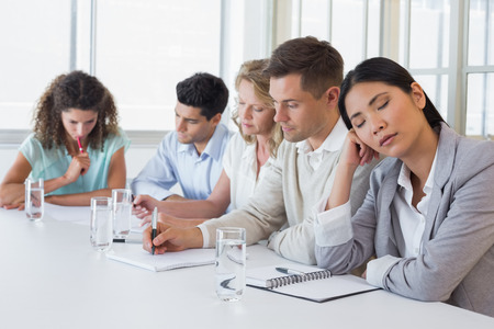 Casual businesswoman falling asleep during meeting in the office photo