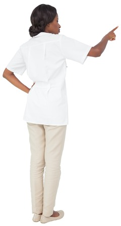 tunic: Young nurse in tunic pointing on white background Stock Photo