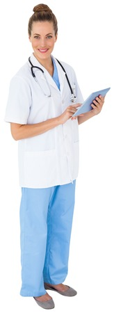 tunic: Pretty nurse in tunic using tablet pc on white background
