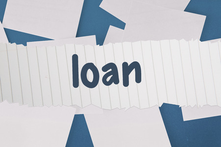 untidy text: The word loan against white paper strewn over blue Stock Photo