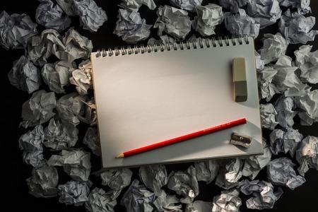 parer: Paper notebook with pencil eraser and parer on dark background