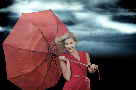 Smiling blonde holding umbrella against stormy dark sky with lightning bolt photo