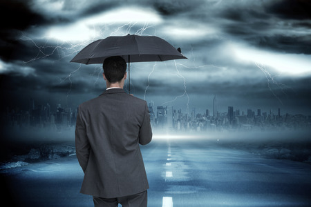 Rear view of classy businessman holding grey umbrella against stormy sky with tornado over road photo