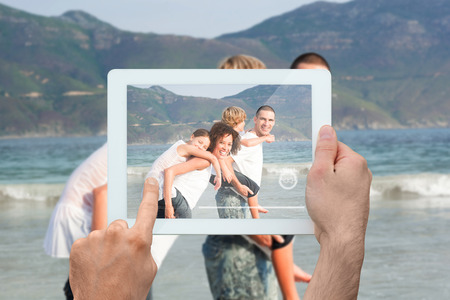 Hand holding tablet pc showing family having fun at the beach photo