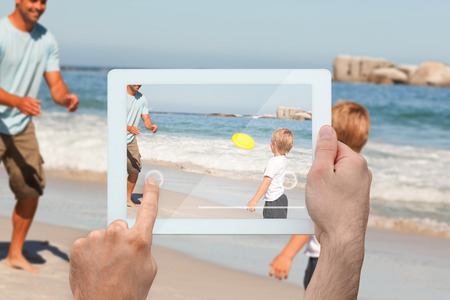 Hand holding tablet pc showing father playing frisbee with son at beach photo
