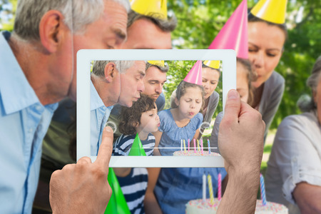 Hand holding tablet pc showing family celebrating little girls birthday in the park photo