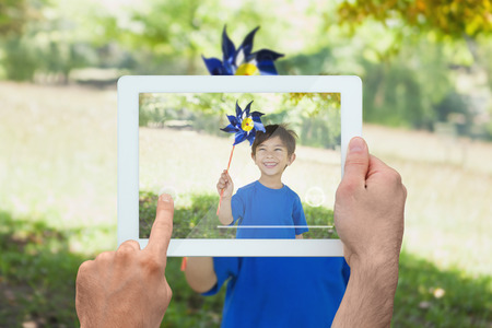 Hand holding tablet pc showing little boy holding pinwheel in park photo