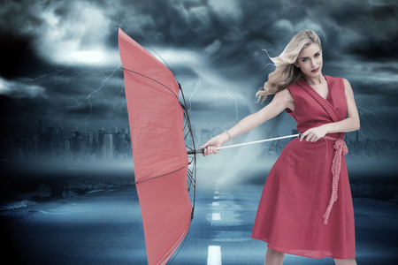 Elegant blonde holding umbrella against stormy sky with tornado over road photo