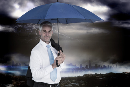 Businessman holding blue umbrella against stormy sky over large city  photo