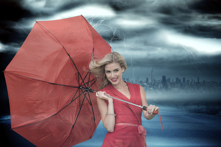 Smiling blonde holding umbrella against stormy sky with tornado over road photo