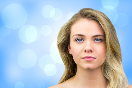 unsmiling: Serious blonde natural beauty against blue abstract light spot design