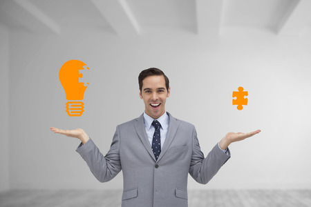 Smiling businessman presenting graphics with his hands against bright white room photo