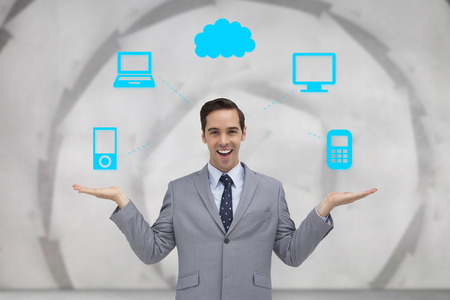 Smiling businessman presenting graphics with his hands against sheet spiral on grey wall photo