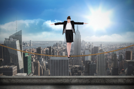 balancing act: Businesswoman performing a balancing act against balcony overlooking city Stock Photo