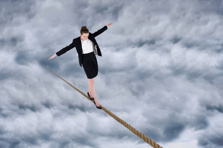 Composite image of businesswoman performing a balancing act against cloudy sky