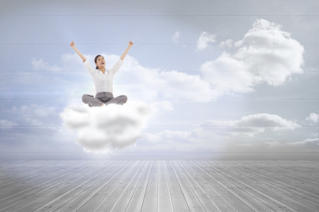 Cheering businesswoman sitting cross legged against clouds in a room photo