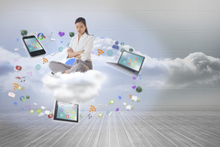 woman looking down: Annoyed businesswoman sitting with arms crossed against clouds in a room Stock Photo