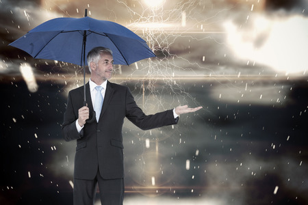 Happy businessman holding umbrella against cloudy sky with snow falling photo