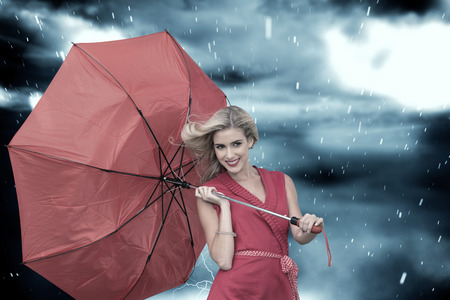 Smiling blonde holding umbrella against cloudy sky with snow falling photo