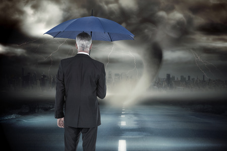 Businessman holding umbrella against stormy sky with tornado over road photo