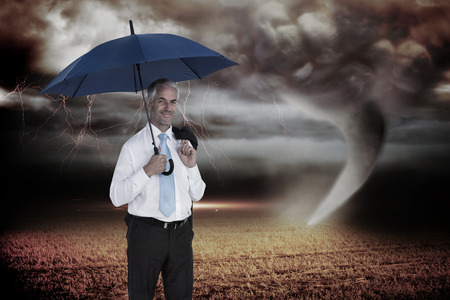 Happy businessman holding umbrella against stormy sky with tornado over field photo