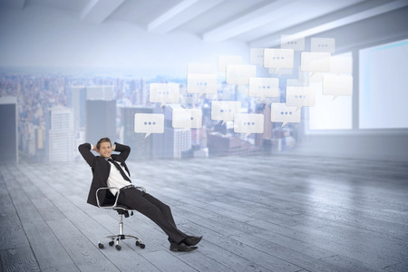 Composite image of businessman sitting on swivel chair against city scene in a room photo
