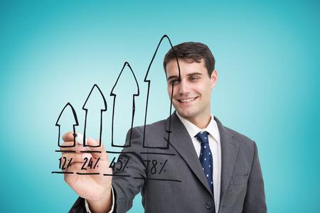 Composite image of businessman drawing graph against blue vignette photo