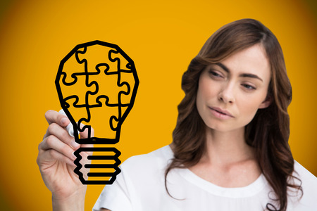 Composite image of businesswoman drawing light bulb against yellow background with vignette photo